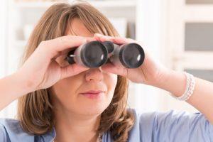 Beautiful woman Looking through binocular at home